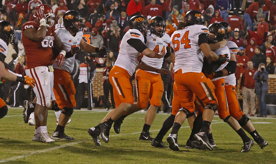 Photo - Oklahoma State celebrates after Ben Grogan (19)  kicked the game-winning field goal in overtime of a Bedlam college football game between the University of Oklahoma Sooners (OU) and the Oklahoma State Cowboys (OSU) at Gaylord Family-Oklahoma Memorial Stadium in Norman, Okla., Saturday, Dec. 6, 2014. Photo by Bryan Terry, The Oklahoman