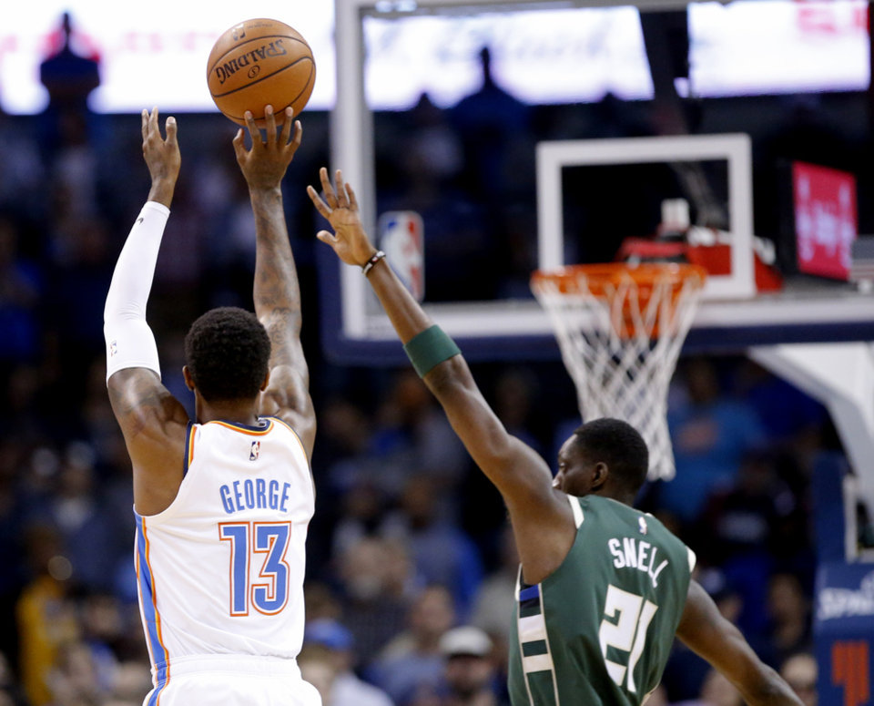 Photo - Oklahoma City's Paul George (13) shoots over Milwaukee's Tony Snell (21)  during a NBA preseason game between the Oklahoma City Thunder and Milwaukee Bucks at Chesapeake Energy Arena in Oklahoma City,  Tuesday, Oct. 9, 2018. Iowa State won 48-42. Photo by Sarah Phipps, The Oklahoman