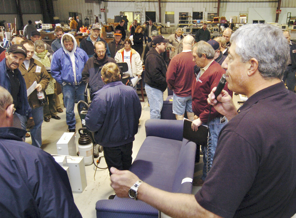 Photo - Auctioneer Louis M. Dakil auctions office equipment and furniture, a small part of the auctioning off the assets of the Downtown Airpark on Dec. 13, 2005. The airport was in receivership, closed and needed cash to pay off it's debts. [THE OKLAHOMAN ARCHIVES]
