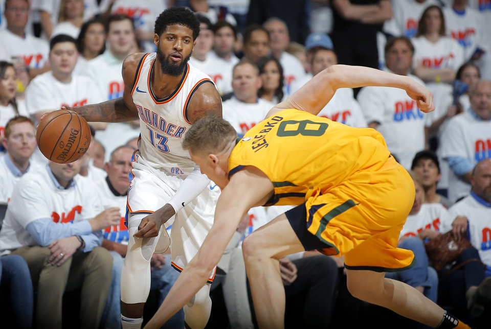 Photo - Utah's Jonas Jerebko (8) falls down in front of Oklahoma City's Paul George (13) during Game 2 of the first round NBA playoff series between the Oklahoma City Thunder and the Utah Jazz at Chesapeake Energy Arena in Oklahoma City, Wednesday, April 18, 2018. Utah won 102-95. Photo by Bryan Terry, The Oklahoman