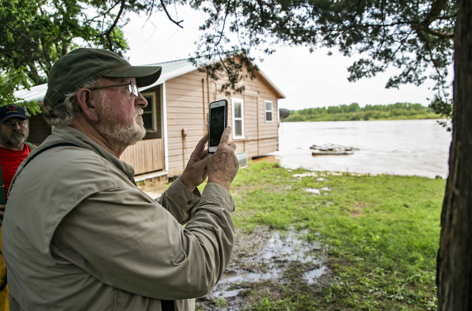 Photo - Omer Catron shoots a photo of the flood waters washing away dirt from under a home as it rushes down the river in the Twin Lakes community near Cimarron City, Okla. on Wednesday, May 22, 2019.  [Chris Landsberger/The Oklahoman]