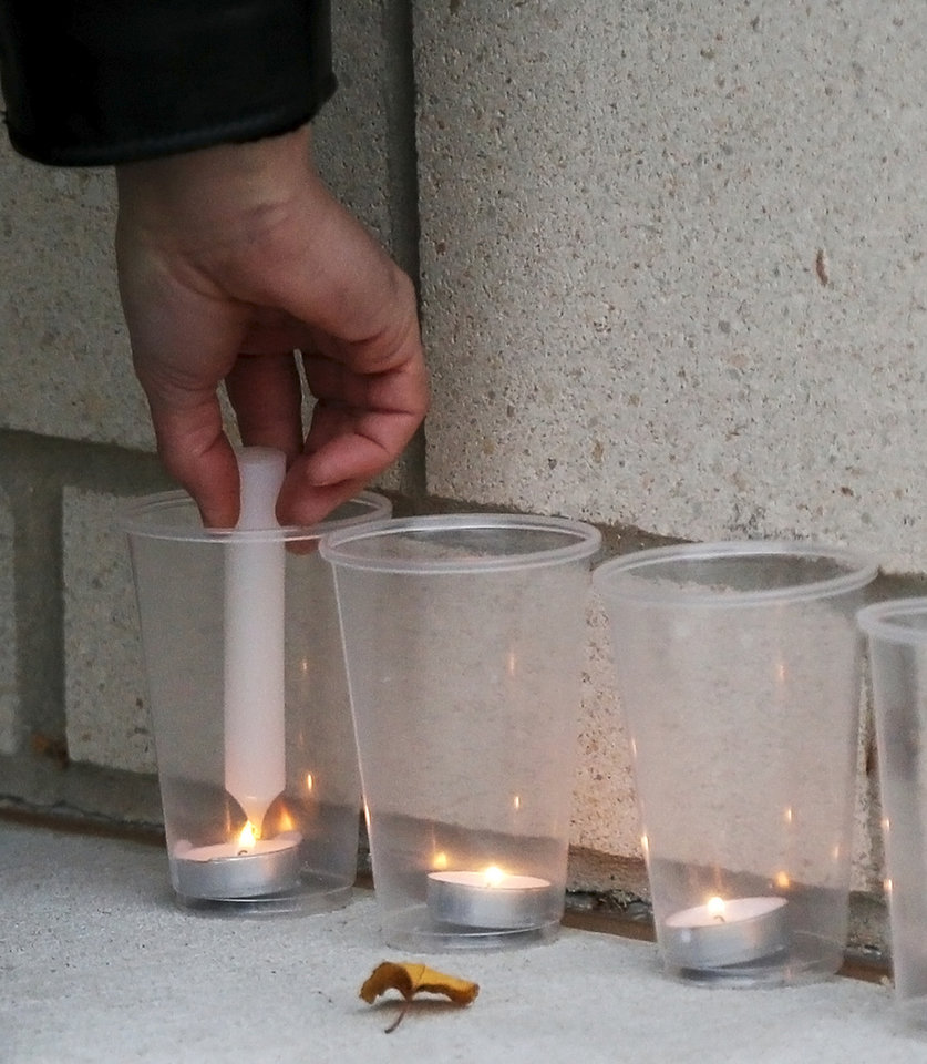 Photo - A man lights a candle during a candlelight vigil outside the Board of Education meeting for Norman Public Schools at 131 S. Flood in Norman, Okla., Monday, Dec. 1, 2014. The vigil was in response to sexual assaults and bullying at Norman High School. Photo by Nate Billings, The Oklahoman