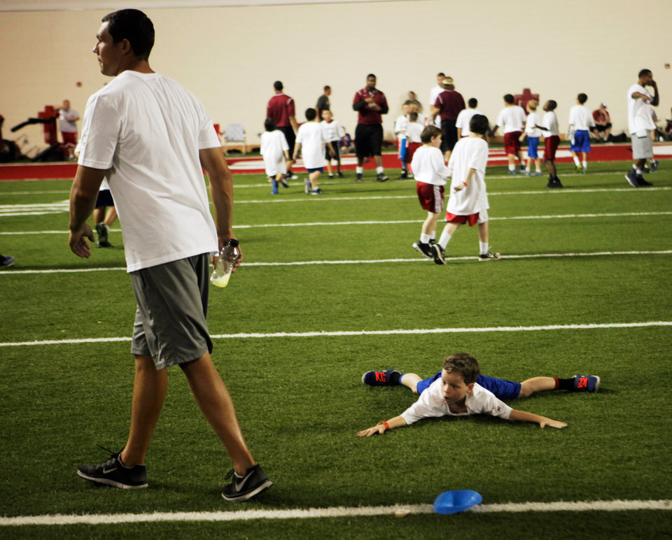 Photo -  Dylan Sullivan, 7, lies flat on the ground in an attempt to catch a glance from Sam Bradford at Bradford's youth football camp held on campus at the University of Oklahoma on July 14, 2013. Photo by KT KING, The Oklahoman