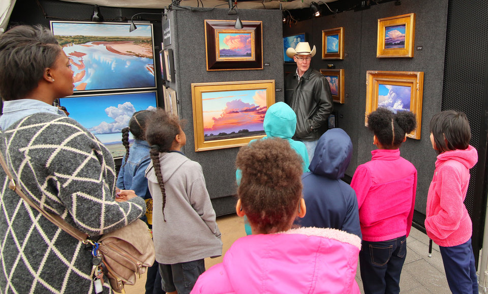 Photo -  Cloudscape artist David J. Holland talks with a school group Wednesday about his work at the Festival of the Arts. [Photo by Doug Hoke, The Oklahoman]