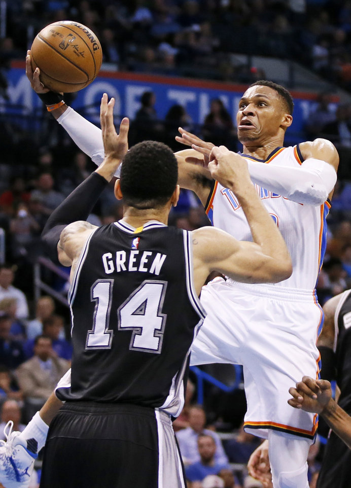 Photo - Oklahoma City's Russell Westbrook (0) takes the ball to the hoop against San Antonio's Danny Green (14) during an NBA basketball game between the Oklahoma City Thunder and San Antonio Spurs at Chesapeake Energy Arena in Oklahoma City, Friday, March 31, 2017. San Antonio won 100-95. Photo by Nate Billings, The Oklahoman