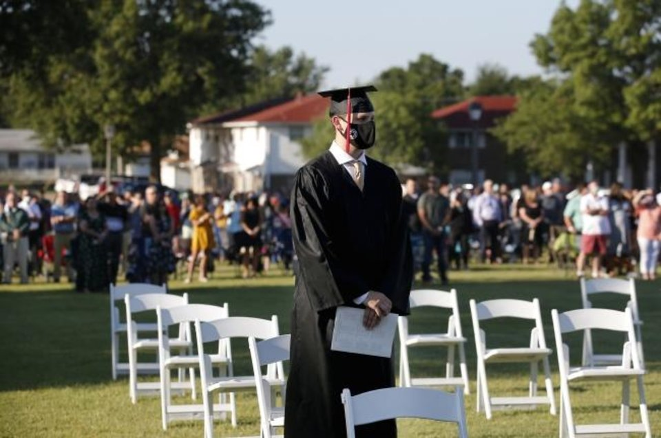 Photo -  Cody Tooley stands during graduation ceremonies outside on the south lawn of the John Wesley Raley Chapel on the campus of Oklahoma Baptist University in Shawnee. [Sarah Phipps, The Oklahoman]