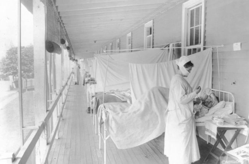 Photo -  A nurse takes the pulse of a patient in the influenza ward of the Walter Reed hospital in Washington in this 1918 file photo provided by the Library of Congress. [Harris & Ewing/Library of Congress via AP]