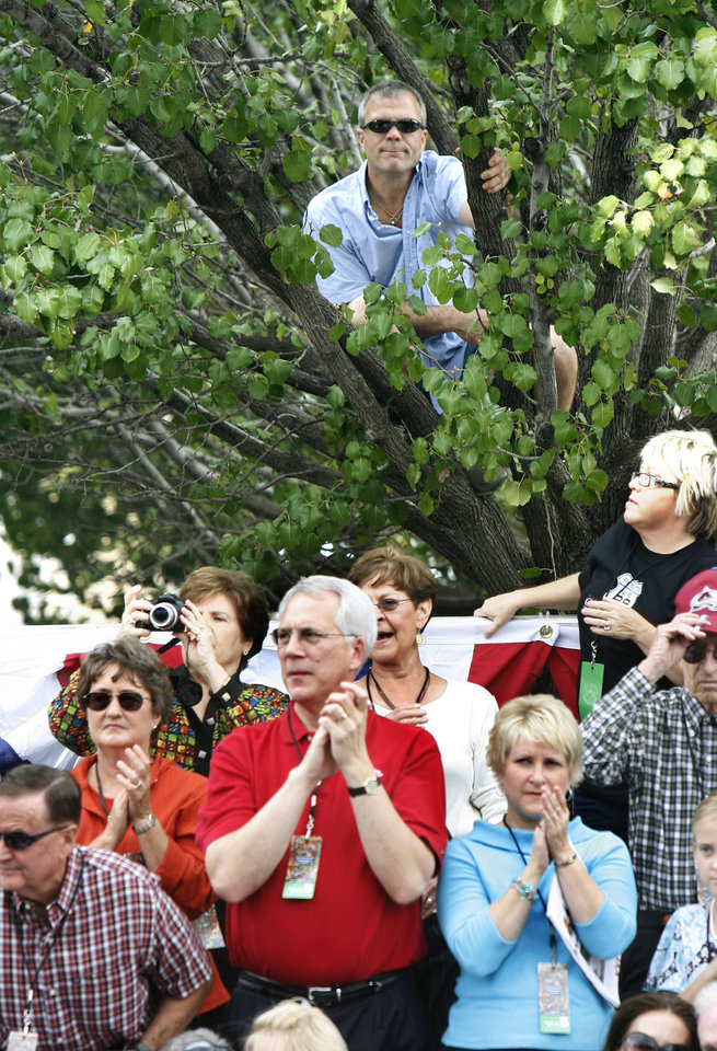 Photo - A spectator watches the Oklahoma Centennial Parade from the branches of a Bradford Pear tree in downtown Oklahoma City, Okla., Sunday, October 14, 2007. Photo by Paul Hellstern / The Oklahoman.