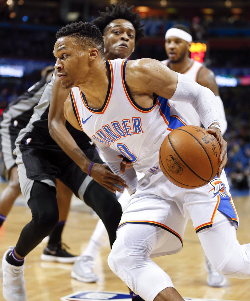 Photo - Oklahoma City's Russell Westbrook (0) drives past Sacramento's De'Aaron Fox (5) during an NBA basketball game between the Oklahoma City Thunder and the Sacramento Kings at Chesapeake Energy Arena in Oklahoma City, Monday, March 12, 2018. Photo by Nate Billings, The Oklahoman