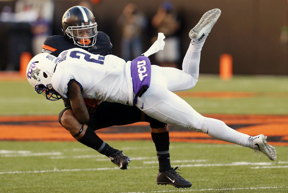 Photo - Oklahoma State's Jordan Sterns (13) tackles TCU's Trevone Boykin (2) on a keeper during the college football game between the Oklahoma State Cowboys (OSU) and TCU Horned Frogs at Boone Pickens Stadium in Stillwater, Okla., Saturday, Nov. 7, 2015. Photo by Nate Billings, The Oklahoman