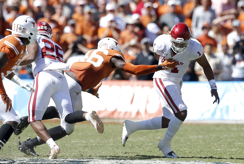 Photo - Oklahoma's Jalen Hurts (1) puts the ball behind his back as he scrambles during the Red River Showdown college football game between the University of Oklahoma Sooners (OU) and the Texas Longhorns (UT) at Cotton Bowl Stadium in Dallas, Saturday, Oct. 12, 2019. OU won 34-27. [Sarah Phipps/The Oklahoman]