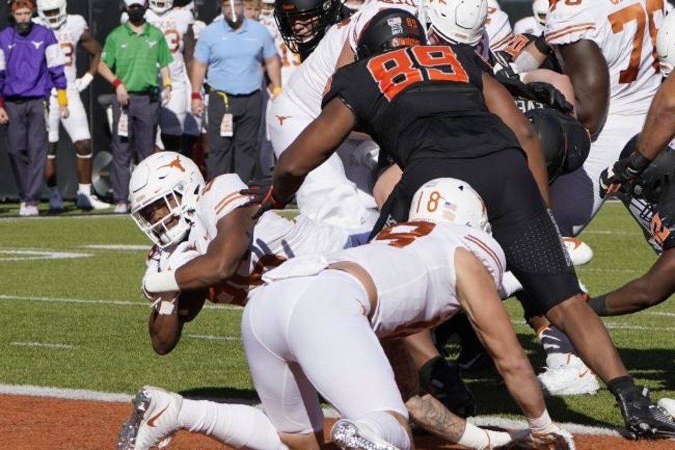 Photo -  Texas running back Keaontay Ingram, left, dives into the end zone for a touchdown in front of Oklahoma State defensive end Tyler Lacy (89) in the first half of an NCAA college football game in Stillwater, Okla., Saturday, Oct. 31, 2020. (AP Photo/Sue Ogrocki)