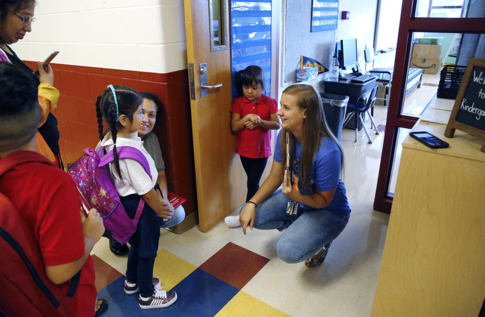 Photo - Kindergarten teacher Kyrianna Mitchell kneels to welcome Reina Camargo to her classroom as she arrives with her family on the first day of school at Cesar Chavez Elementary School on SE Grand Blvd. Students returned to classrooms across the city on Wednesday, Aug. 1, 2018, as Oklahoma City Public Schools started another school year. Photo by Jim Beckel, The Oklahoman