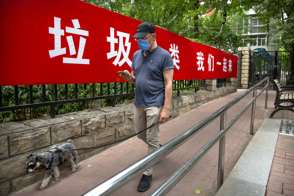 Photo -  A man wearing a face mask to protect against the spread of the new coronavirus walks past a propaganda banner encouraging people to sort their garbage in Beijing, Wednesday, June 24, 2020. New virus cases have declined in China and in the capital Beijing, where a two-week spike appears to be firmly waning. (AP Photo/Mark Schiefelbein)