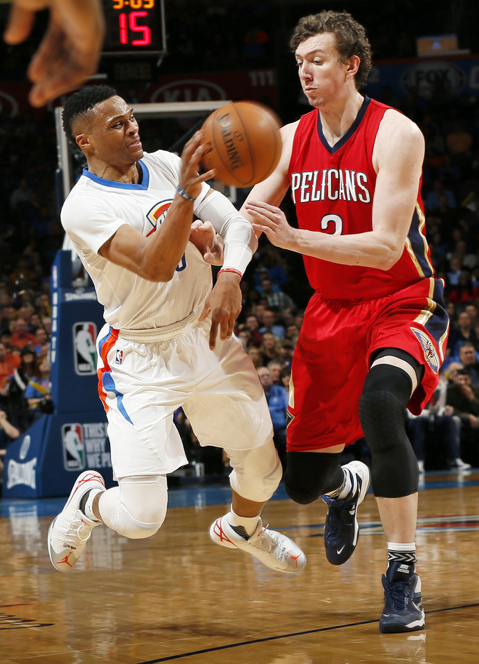 Photo - Oklahoma City's Russell Westbrook (0) tries to pass away from New Orleans' Omer Asik (3) during an NBA basketball game between the New Orleans Pelicans and the Oklahoma City Thunder at Chesapeake Energy Arena in Oklahoma City, Thursday, Feb. 11, 2016.  Photo by Nate Billings, The Oklahoman