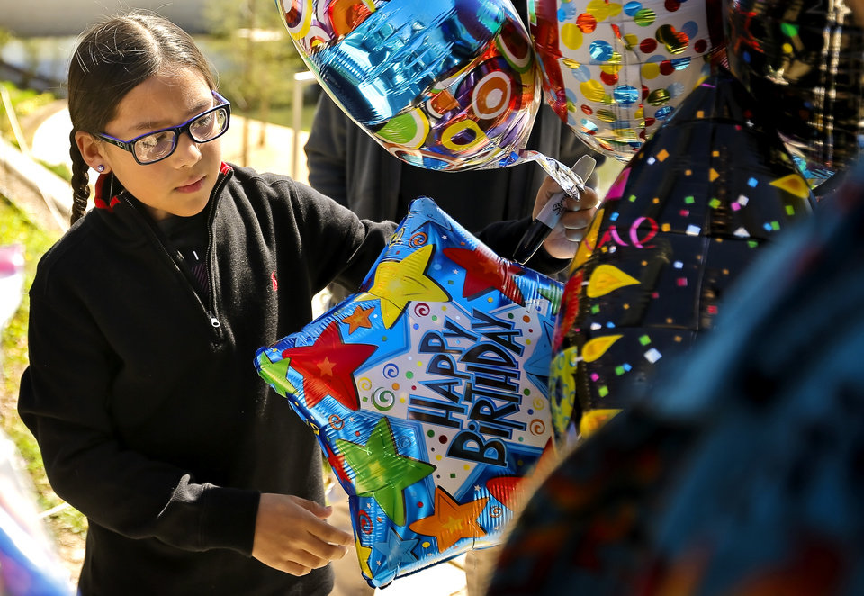Photo - Jaylon Wahnee picks out a balloon to write a message on as he prepares to release the balloon in honor of his uncle Bradley Wahnee, who was killed in 2009 during a drive by shooting, to mark his birthday at the Myriad Botanical Gardens in Oklahoma City, Okla. on Monday, March 21, 2016. The family releases balloons every year on Bradley's birthday and the date he was killed.  Photo by Chris Landsberger, The Oklahoman