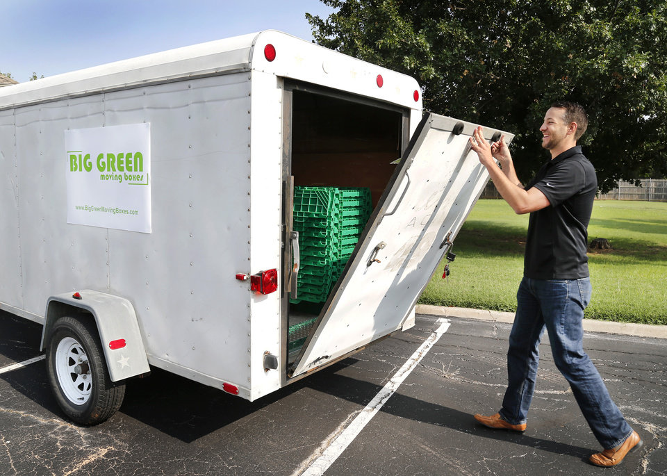 Photo -  Steven Embree opens a trailer containing reusable moving boxes Tuesday. Embree and his business partner, Matt Damiani, are launching a moving box rental business in the Oklahoma City area called Big Green Moving Boxes. [Photos by Jim Beckel, The Oklahoman]