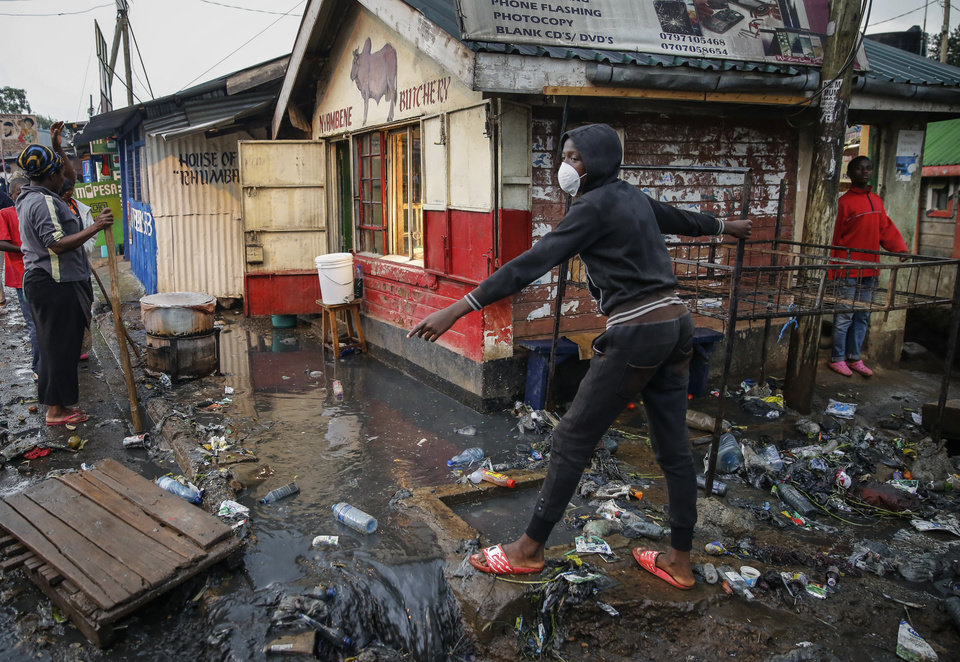 Photo -  FILE - In this Thursday, March 26, 2020 file photo, a boy wears a mask as a preventative measure against the spread of the new coronavirus, as he navigates a flood of water mixed with garbage following heavy rains, in the Kibera slum, or informal settlement, of Nairobi, Kenya. Up to 150 million people could slip into extreme poverty, living on less than $1.90 a day, by late next year depending on how badly economies shrink during the COVID-19 pandemic, the World Bank said Wednesday, Oct. 7, 2020 in an outlook grimmer than before. (AP Photo/Brian Inganga, File)
