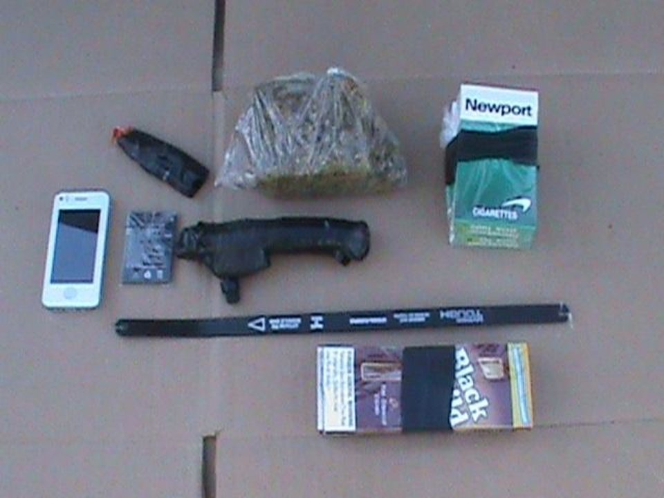 Photo -  Contraband carried by a drone into the Oklahoma State Penitentiary in McAlester. The package included super glue, a cellphone and battery, cigars and cigarettes, methamphetamine, heroin, marijuana, and hacksaw blades. The drone crashed shortly after entering the facility. Photo provided by the Oklahoma Department of Corrections.