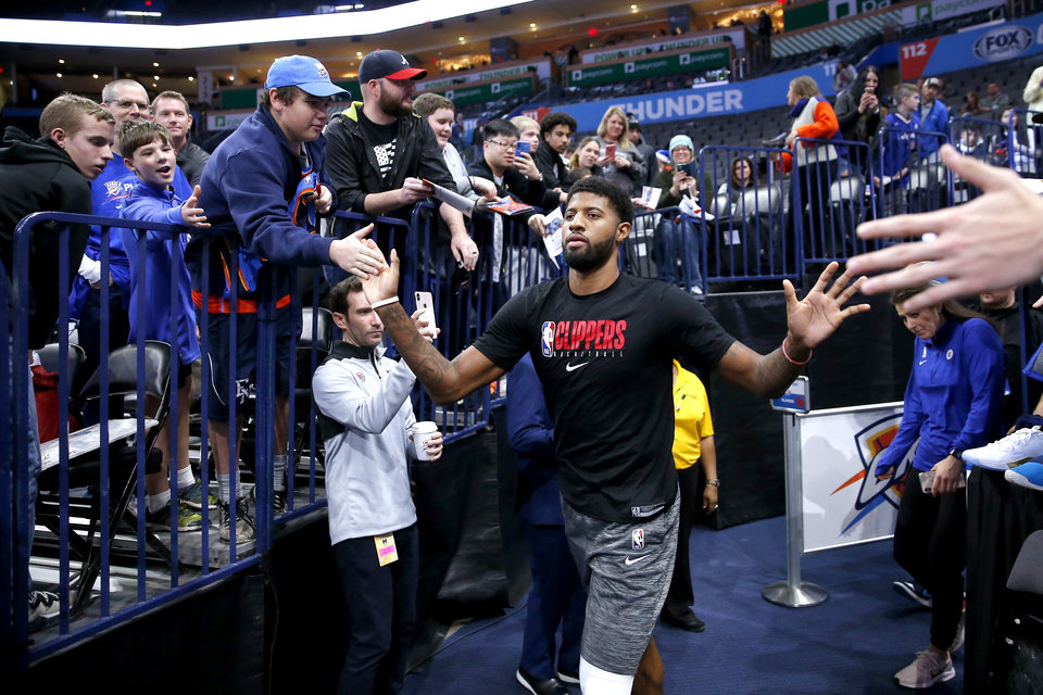Photo - Paul George with the LA Clippers is greeted by fans as he walks to the court before an NBA basketball game between the Oklahoma City Thunder and the LA Clippers at Chesapeake Energy Arena in Oklahoma City, Sunday, Dec. 22, 2019. [Bryan Terry/The Oklahoman]
