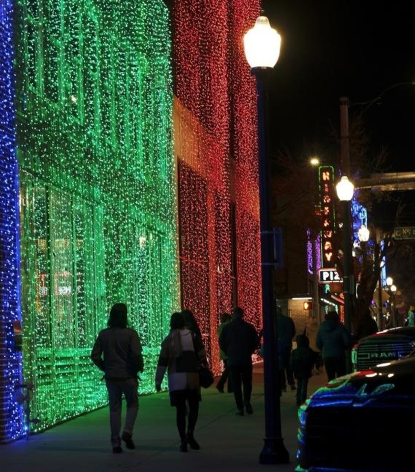 Photo -  People make their way north on Broadway Avenue in Automobile Alley. The historic downtown OKC district dazzles this time of year, with more than 230,000 kaleidoscopic LED lights curtaining the buildings along 10 blocks of North Broadway and the side streets through Jan. 10. [Doug Hoke/The Oklahoman]