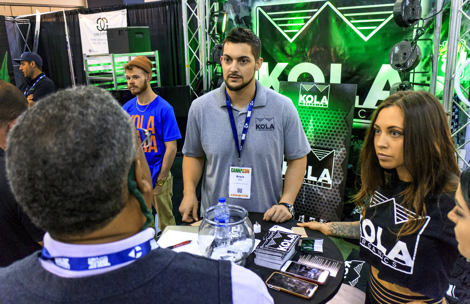 Photo - Bryce Davis, Kola Organics, talks to people at his booth set up during the Oklahoma City CannaCon at the Cox Convention Center in Oklahoma City, Okla. on Wednesday, April 17, 2019.   Photo by Chris Landsberger, The Oklahoman