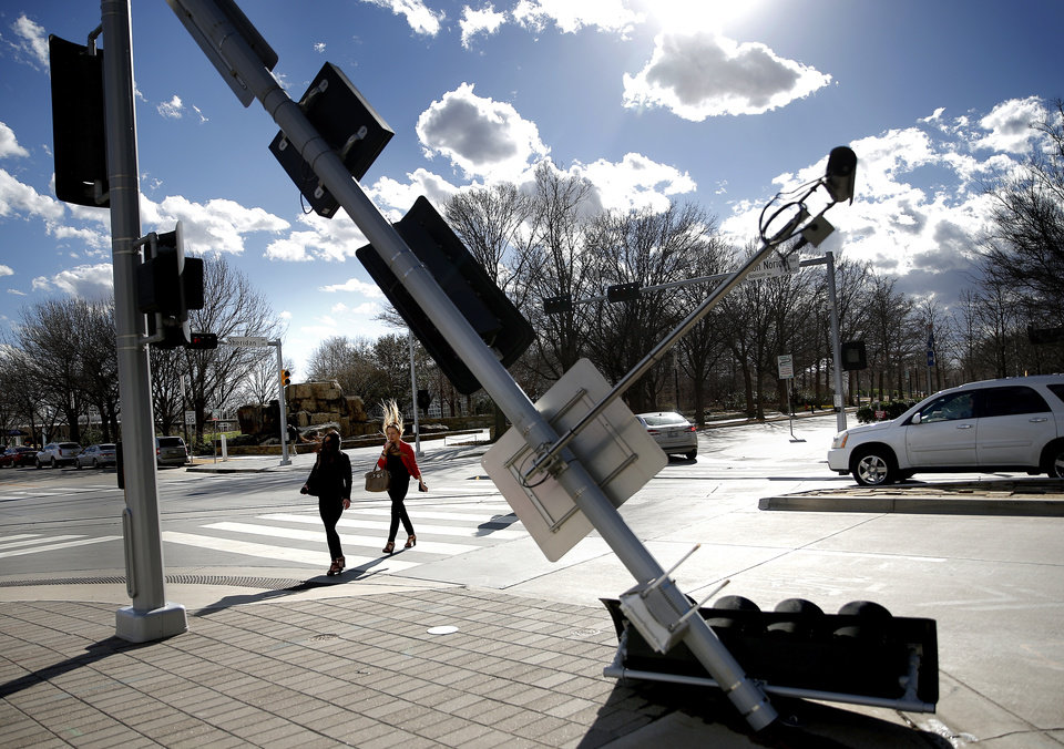 Photo - Pedestrians cross West Sheridan at South Robinson Ave.m just after the wind knocked the West Sheridan traffic light down in downtown Oklahoma City,  Wednesday, March 13, 2019. Photo by Sarah Phipps, The Oklahoman