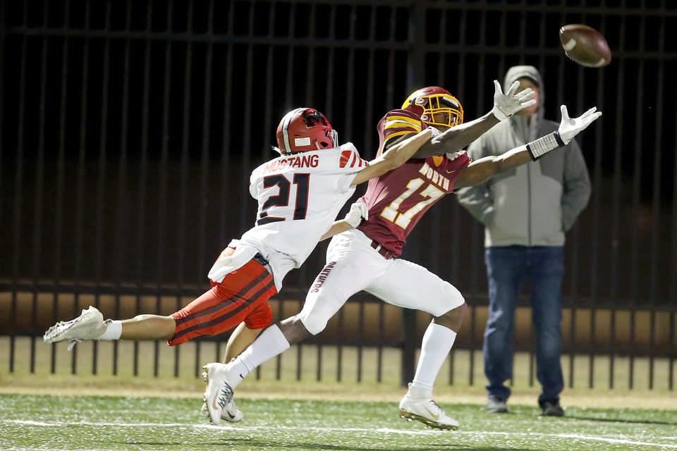 Photo - The ball goes past Putnam City's Angelo Bell as Mustang's Karton Keene defends during a high school football game between Putnam City North and Mustang in Oklahoma City, Friday, Nov. 1, 2019.  [Bryan Terry/The Oklahoman]