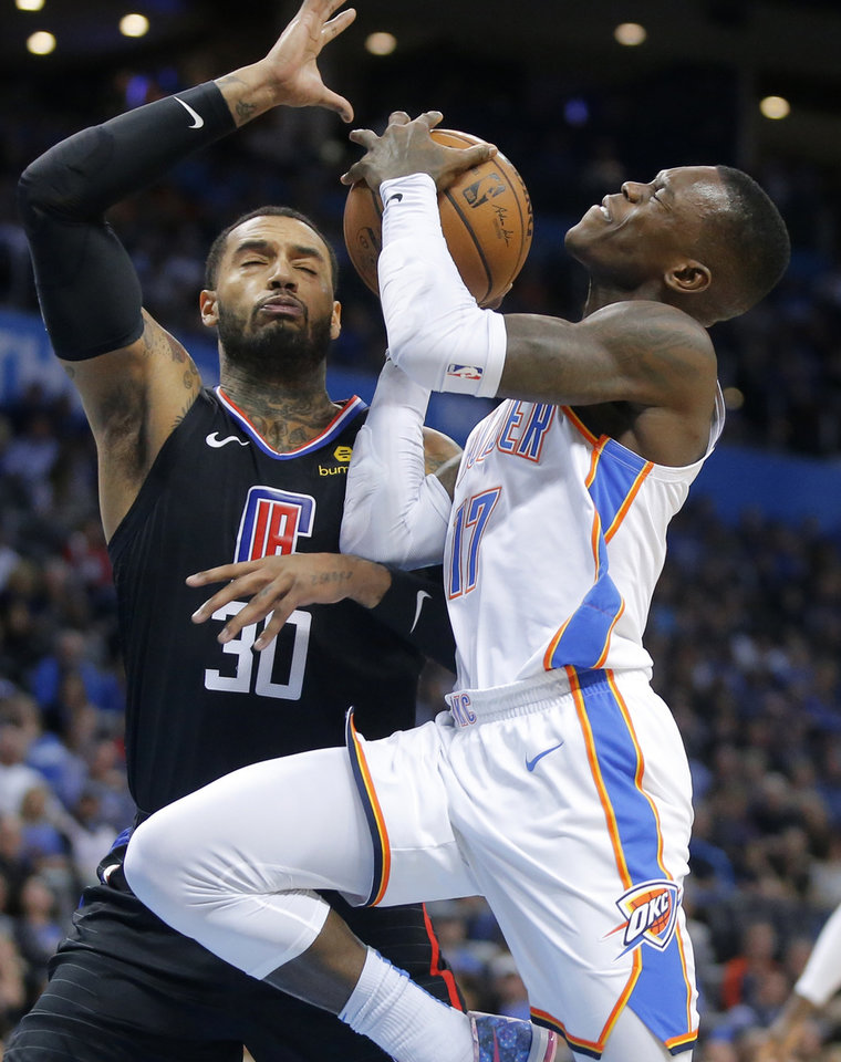 Photo -  Oklahoma City's Dennis Schroder, right, tries to get past Mike Scott of the Los Angeles Clippers during a game in December at Chesapeake Energy Arena. The Thunder, Clippers and San Antonio Spurs are jockeying for playoff position in the Western Conference. [Bryan Terry/The Oklahoman]