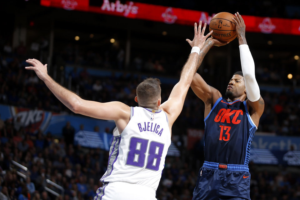 Photo - Oklahoma City's Paul George (13) shoots over Sacramento's Nemanja Bjelica (88) during an NBA basketball game between the Oklahoma City Thunder and the Sacramento Kings at Chesapeake Energy Arena in Oklahoma City, Sunday, Oct. 21, 2018. Photo by Bryan Terry, The Oklahoman