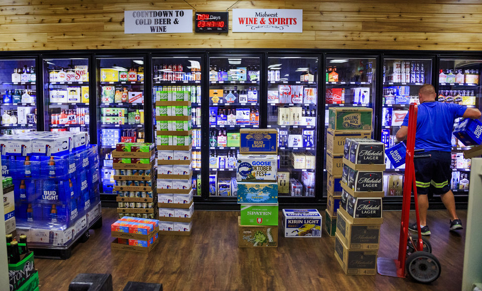 Photo -  The countdown clock at Midwest Wine & Spirits ticks away to October 1 as work continues to get the store's coolers stocked with high-point beer on Wednesday. [Photo by Chris Landsberger, The Oklahoman]