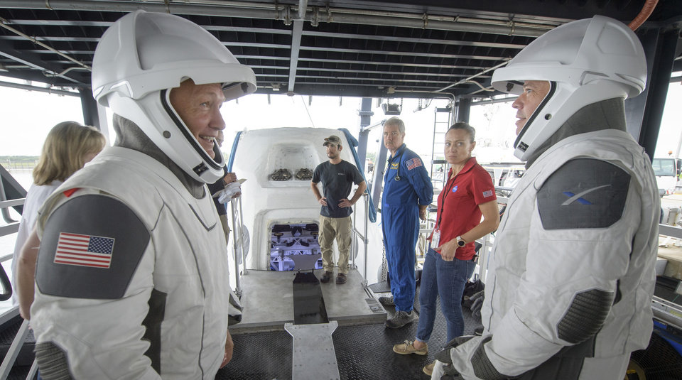 Photo -  NASA astronauts Doug Hurley, left, and Bob Behnken work with teams from NASA and SpaceX, Aug. 13, to rehearse crew extraction from SpaceX's Crew Dragon, which will be used to carry humans to the International Space Station, at the Trident Basin in Cape Canaveral, Fla. [Bill Ingalls/NASA via The Associated Press]