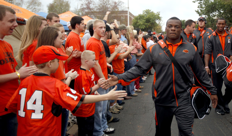 Photo - OSU's Kendall Hunter gives fans high fives during the Spirit Walk before the college football game between the Oklahoma State Cowboys (OSU) and the Nebraska Huskers (NU) at Boone Pickens Stadium in Stillwater, Okla., Saturday, Oct. 23, 2010. Photo by Sarah Phipps, The Oklahoman