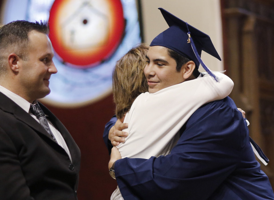 Photo - Joshua gets a hug from Laneta Going as Douglas McPherson watches after his introduction during the Teen Recovery Solutions (TRS) at Mission Academy high school graduation ceremony at St. Paul's Episcopal Cathedral, 127 NW 7th, in Oklahoma City, Thursday, May 26, 2016. Photo by Doug Hoke, The Oklahoman