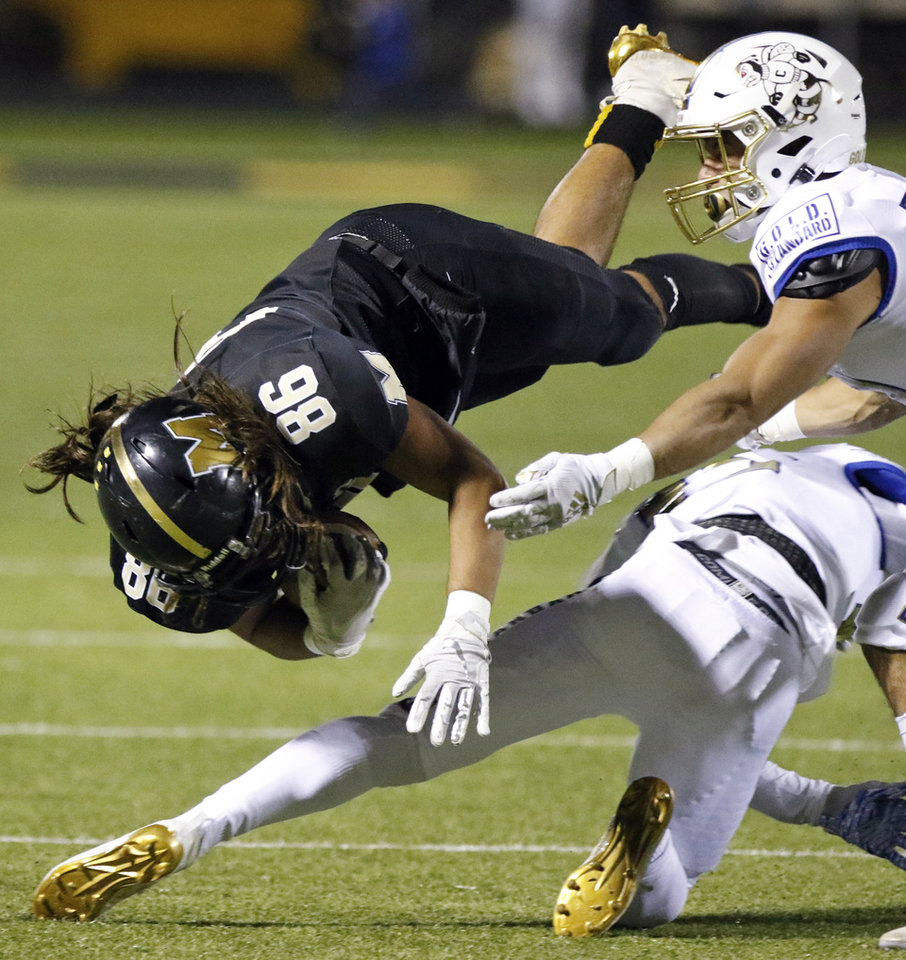 Photo - Midwest City's Wesley Dedmon (86) is tripped up after a catch during a high school football game between Midwest City and Choctaw at Rose Field in Midwest City, Okla., Friday, Nov. 1, 2019. [Nate Billings/The Oklahoman]