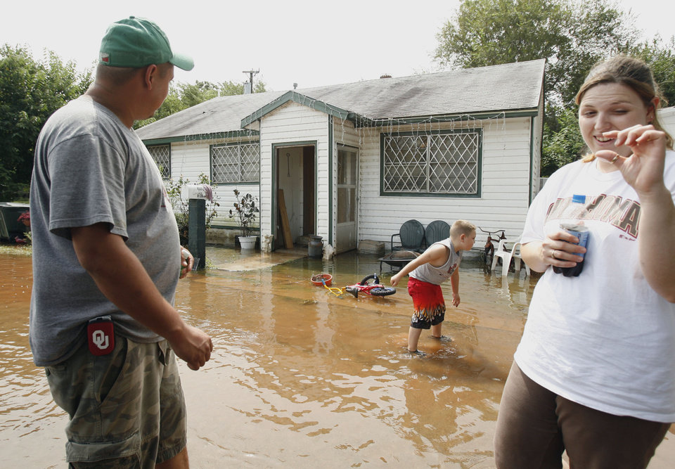 Photo - Michele Rouse shows the gap between the water and her floor when they awoke Sunday morning.  She, husband Brandon (left) and six-year-old Brayden were awakened early Sunday by a family member alerting them to flood waters.   Water from a nearby creek was within an inch of pouring into their home on the north side of Lindsay, Oklahoma on Sunday, August 19, 2007.   BY STEVE SISNEY, THE OKLAHOMAN