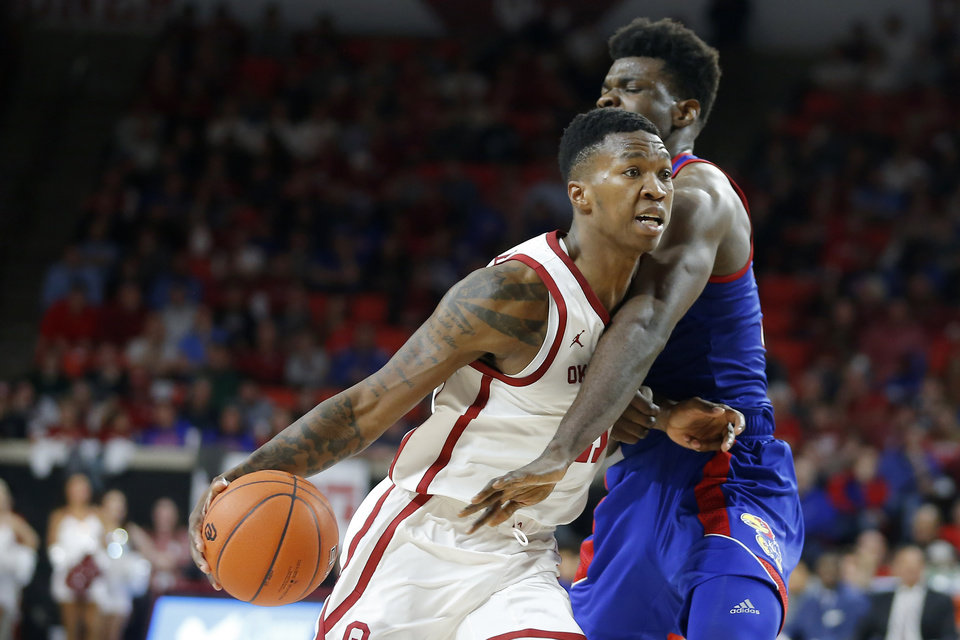 Photo - Oklahoma's Kristian Doolittle (21) goes past Kansas' Udoka Azubuike (35) during an NCAA college basketball game between the University of Oklahoma Sooners (OU) and the University of Kansas Jayhawks at Lloyd Noble Center in Norman, Okla., Tuesday, Jan. 14, 2020. Oklahoma lost 66-52.  [Bryan Terry/The Oklahoman]