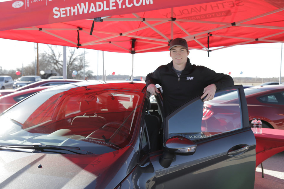 Photo - Austin Mayes stands next to his 2016 Ford Fiesta on Thursday at Seth Wadley Ford in Pauls Valley. Mayes won a car by hitting a halfcourt shot at an Oklahoma City Blue game on Saturday, Feb. 6, 2016. Photo provided.