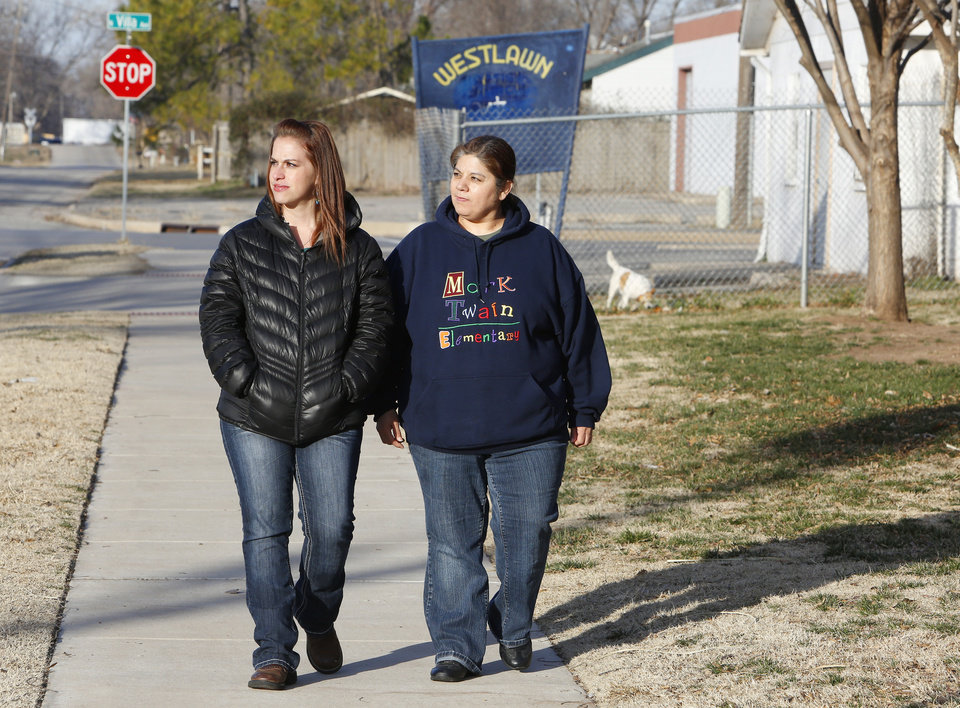Photo -  Mark Twain Elementary School kindergarten teacher Kristen Widener and school district bilingual assistant Toni Ramirez walk Friday in the Westlawn neighborhood while conducting parent-teacher conferences at homes in Oklahoma City. Photo by Paul B. Southerland, The Oklahoman   PAUL B. SOUTHERLAND -  PAUL B. SOUTHERLAND
