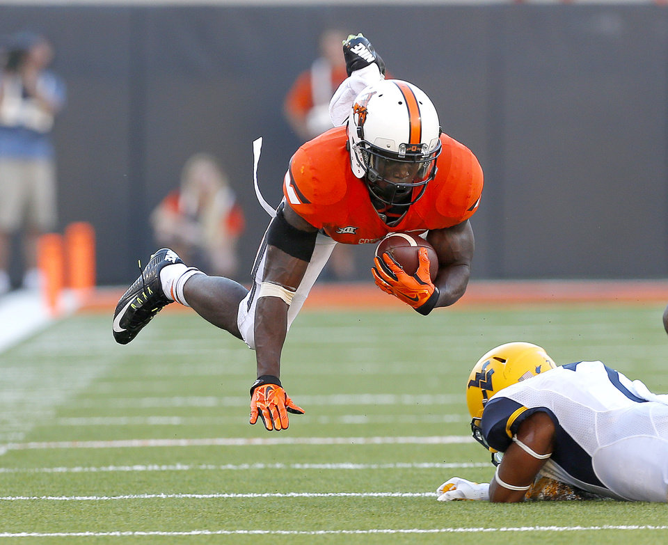 Photo - Oklahoma State's Tyreek Hill (24) leaps forward after being tackled by West Virginia's Daryl Worley (7) during a college football game between the Oklahoma State University Cowboys (OSU) and the West Virginia Mountaineers (WVU) at Boone Pickens Stadium in Stillwater, Okla., Saturday, Oct. 25, 2014.  West Virginia won 34-10. Photo by Sarah Phipps, The Oklahoman