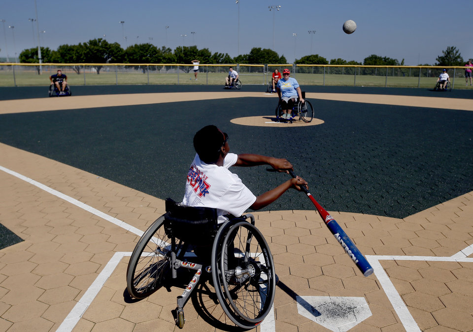 Photo -  J-Rod Denning, 13, bats during a wheelchair softball contest at the Endeavor Games at Mitch Park in Edmond on Sunday. [PHOTO BY SARAH PHIPPS, THE OKLAHOMAN]