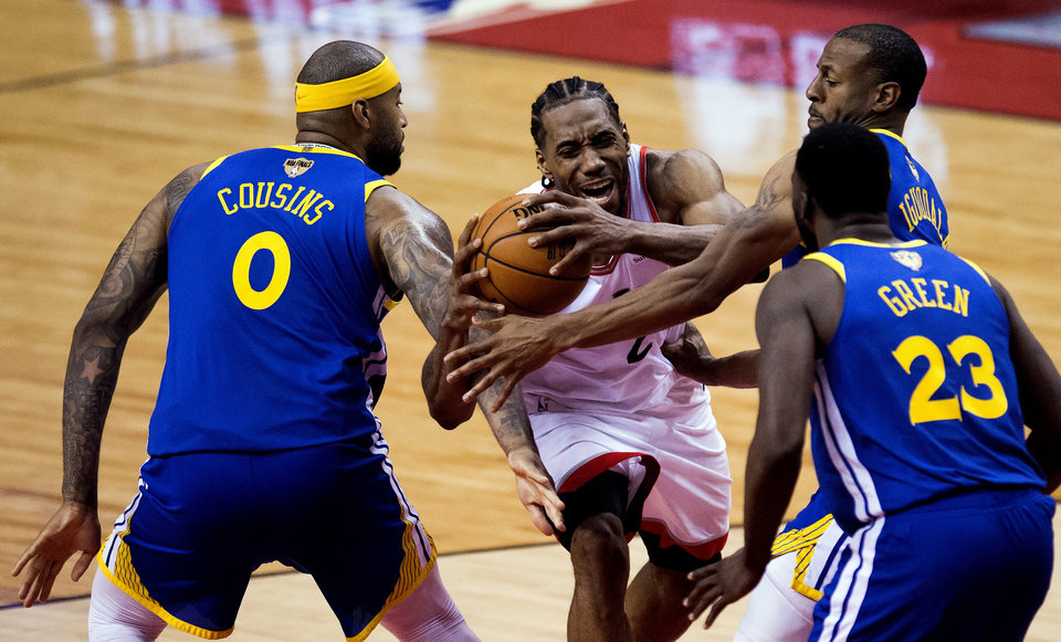 Photo - Toronto Raptors forward Kawhi Leonard (2) draws a foul as he drives to the net against Golden State Warriors center DeMarcus Cousins (0), forward Draymond Green (23) and forward Andre Iguodala (9) during second-half basketball action in Game 5 of the NBA Finals in Toronto, Monday, June 10, 2019. (Chris Young/The Canadian Press via AP)