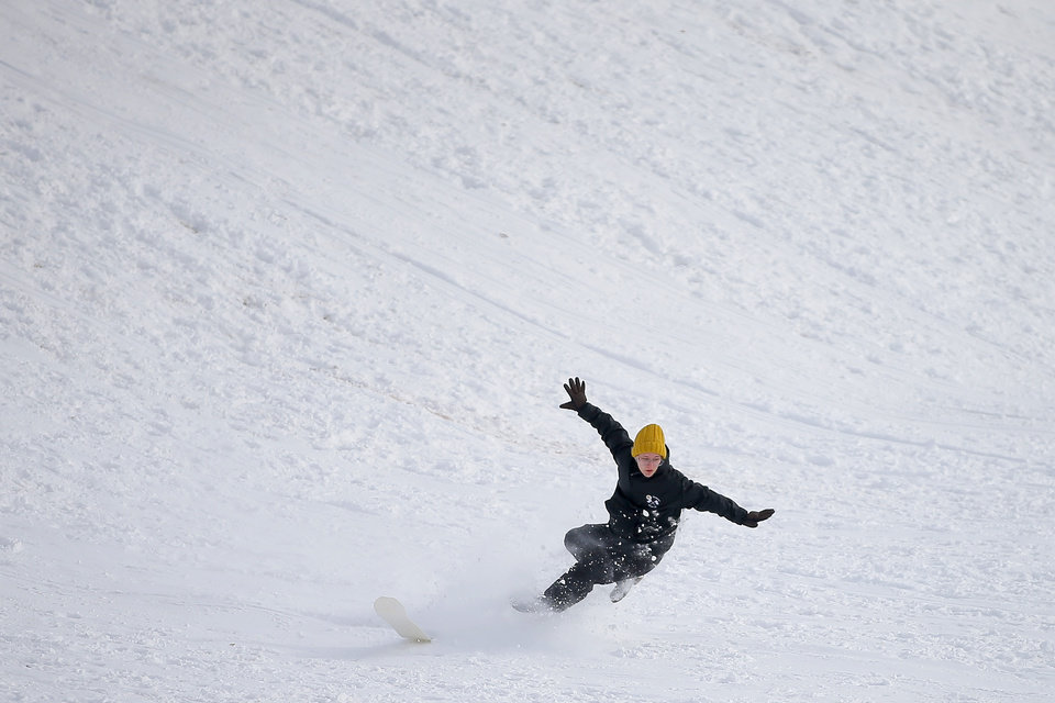 Photo - A person falls down while sledding down a hill along W Hefner Road in Oklahoma City after a winter storm dropped another layer of snow in Oklahoma City, Wednesday, Feb. 17, 2021. [Bryan Terry/The Oklahoman]