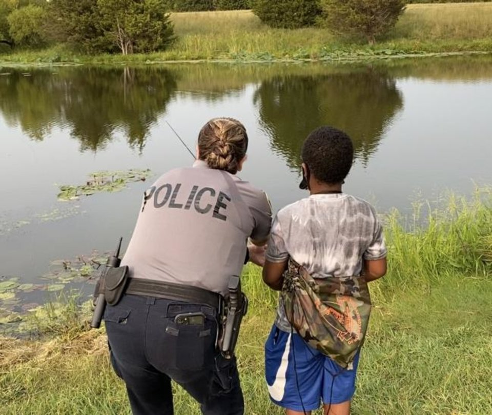 Photo -  A police officer assists a young boy while fishing during a fishing clinic for foster children sponsored by the Oklahoma Department of Wildlife Conservation and the Department of Human Services. [PHOTO PROVIDED BY OKLAHOMA WILDLIFE CONSERVATION FOUNDATION]