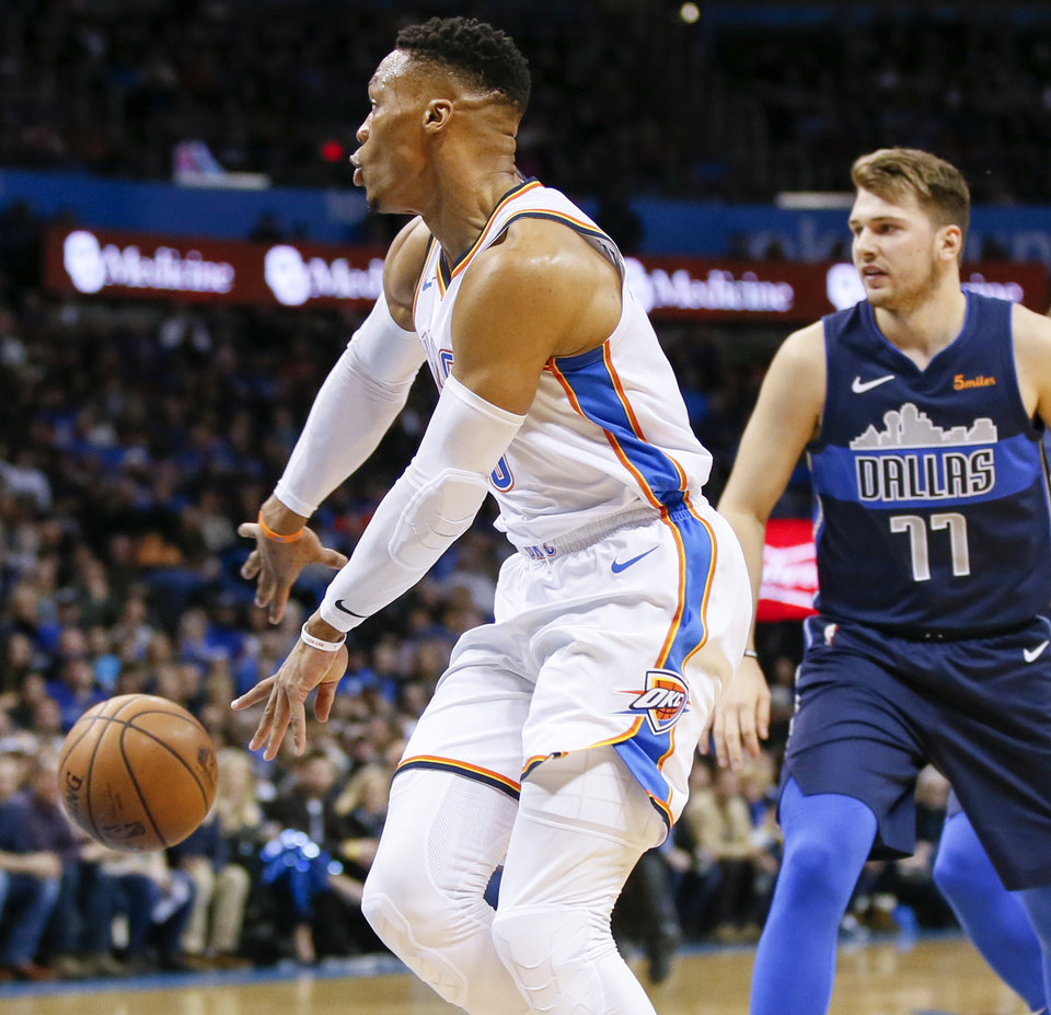 Photo - Oklahoma City's Russell Westbrook (0) passes in front of Dallas' Luka Doncic (77) during an NBA basketball game between the Oklahoma City Thunder and Dallas Mavericks at Chesapeake Energy Arena in Oklahoma City, Monday, Dec. 31, 2018. Photo by Nate Billings, The Oklahoman