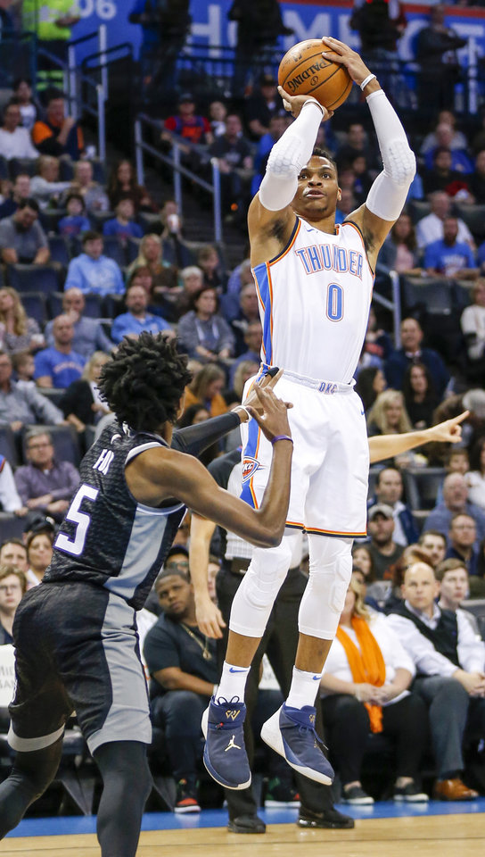 Photo - Oklahoma City's Russell Westbrook (0) shoots over Sacramento's De'Aaron Fox (5) during an NBA basketball game between the Oklahoma City Thunder and the Sacramento Kings at Chesapeake Energy Arena in Oklahoma City, Monday, March 12, 2018. Photo by Nate Billings, The Oklahoman