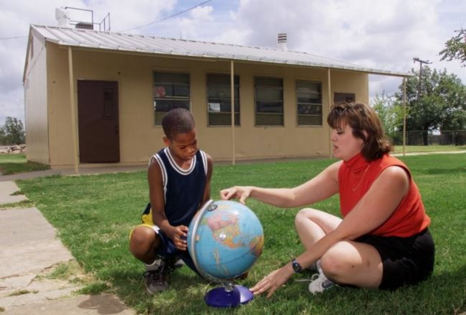 Photo -  North Highland Elementary School 5th grade teacher Amy Leazer uses a globe to go over some geography with 5th grader Donnell Barnett outside the portable classroom Leazer used for her classes prior to the passage of MAPS for Kids. North Highland, like several schools, had used portable classrooms since the mid -1980s.[The Oklahoman Archives]
