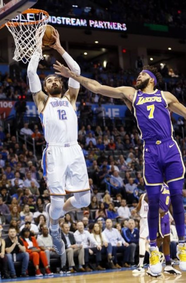 Photo -  Oklahoma City's Steven Adams (12) dunks the ball next to Los Angeles' JaVale McGee (7) in the first quarter during an NBA basketball game between the Los Angeles Lakers and the Thunder's win over the Lakers on Tuesday night at Chesapeake Energy Arena. [Nate Billings/The Oklahoman]