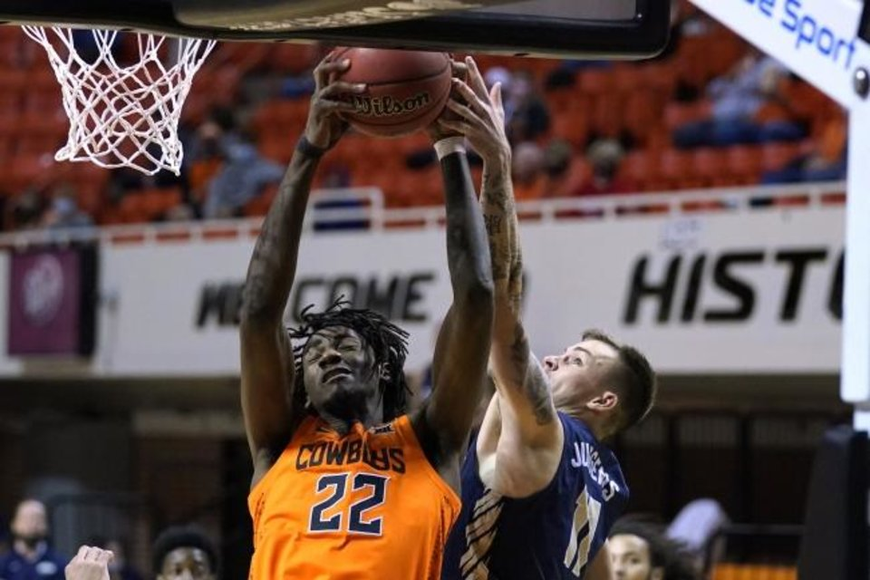 Photo -  Oklahoma State forward Kalib Boone (22) grabs a rebound next to Oral Roberts guard Carlos Jurgens (11) during a Cowbo win on Dec. 8 in Stillwater. [AP Photo/Sue Ogrocki]