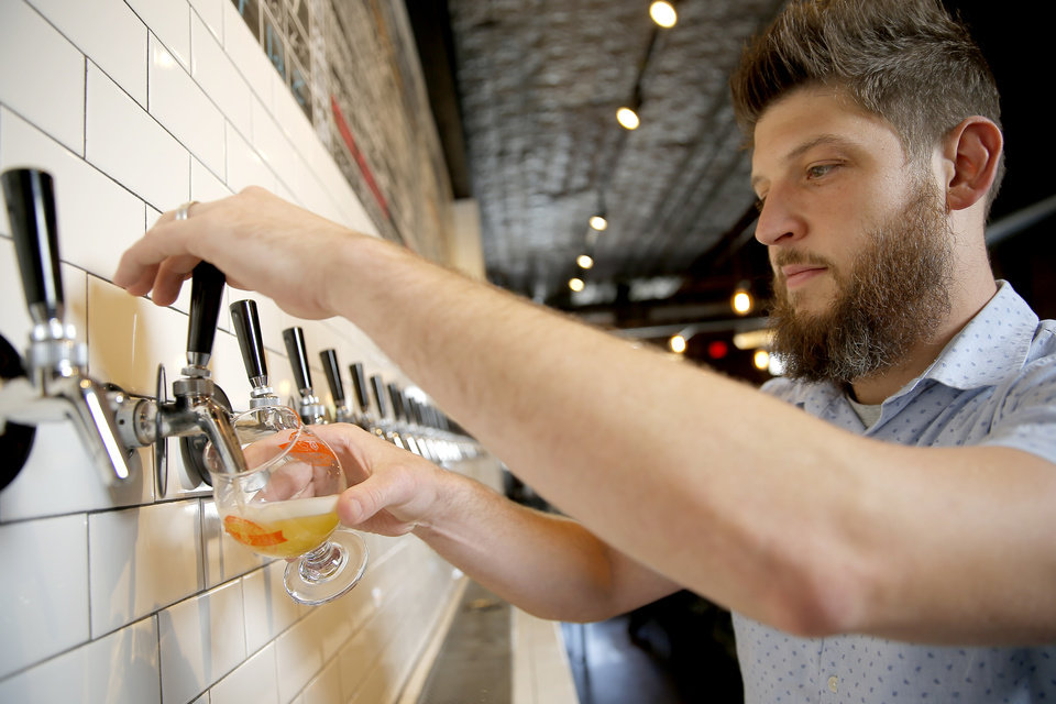 Photo -  Micah Andrews, owner of Oak & Ore and founder of the annual Craft Brew Summit, pours a beer in Oklahoma City on Aug. 23. [Photo by Bryan Terry, The Oklahoman Archives]